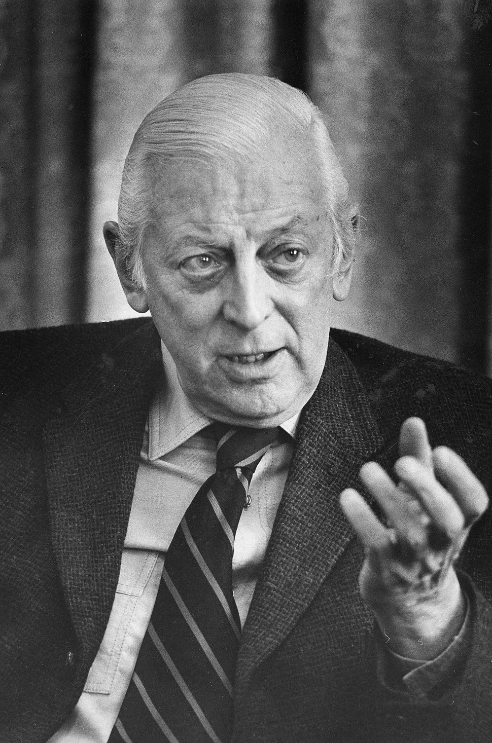 Alistair Cooke, head-and-shoulders portrait, facing front, gesturing with left hand, during interview, March 18, 1974