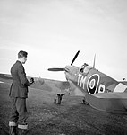 An engine fitter watches the CO of No. 504 Squadron, Squadron Leader R. Lewis, in his Spitfire Mk VC at Middle Wallop, December 1942. CH8010.jpg