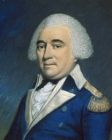 A man with white hair, wearing a blue jacket with gold lapels, buttons, and epaulets, a white shirt, and a black tie