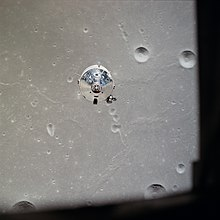 The top of the silvery command module is seen over a gray, cratered lunar surface
