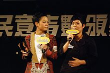 An image of two Asian women holding microphones while standing on a stage.