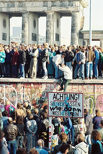 "German reunification - Berlin Wall at the Brandenburg Gate, 9 November 1989. Note the graffiti Wie denn (""How now"") over the sign warning the public that they are leaving West Berlin"