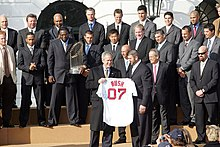 "Two rows of men in suits, one holding a large trophy, stand while a smiling man stands in front of them holding a white baseball jersey which reads ""BUSH 07"" on the back."