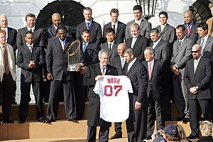 "Several men in suits stand behind a man holding a white baseball jersey which reads ""BUSH 07"" on it."