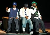 Three African-American men sitting next to each other on a black stage. They are all wearing caps with jeans and sneakers.