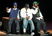 Tri afro-amerikanaj viroj sidante plej proksime al unu la alian sur nigra scenejo. Ili estas ĉiuj elĉerpaj ĉapoj kun ĝinzo kaj gimnastaj ŝuoj.