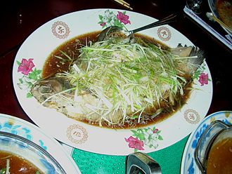 Chinese cuisine - Steamed whole perch with roe inside. Sliced ginger and spring onion is usually spread on top.
