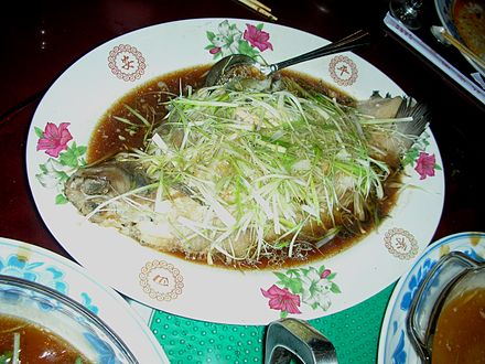 Steamed whole perch with roe inside. Sliced ginger and spring onion is usually spread on top.