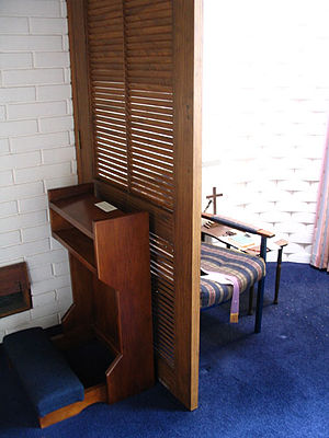 Confession (religion) - Modern confessional in the Church of the Holy Name, Dunedin, New Zealand. The penitent may kneel on the kneeler or sit in a chair facing the priest (not shown)