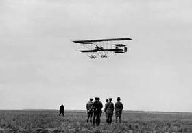 Biplane flying low over field, watched by a group of men