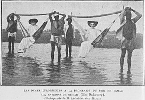 Western European colonialism and colonization - European colonial women being carried in hammocks by natives in Ouidah, Benin (known as French Dahomey during this period).