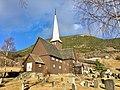 Fåvang Church (kirke) c. 1630, at Tromsnesvegen, Fåvang, Ringebu, Gudbrandsdalen, Oppland, Norway. Graveyard (kirkegård), gate, springtime, farms, Korstadkampen, etc. 2017-04-05 4050.jpg