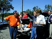 A group of eight middle-aged people surround the open back of a pickup truck that is carrying orange traffic cones and white food containers. The scene is next to a body of water and some trees and a telephone pole, on a blue sky sunny day. Three people are most prominent. One man is dressed in blue pants, and orange T-shirt from a hazardous materials team, and a blue and orange baseball cap. Another man is pointing at an unseen object, and is wearing blue jeans and a dark blue shirt, and has an air of authority about him. A woman is standing next to that man, listening. She is wearing black pants, a white shirt, and has brown hair cut above and down behind the ear and is wearing a thin black wristwatch.
