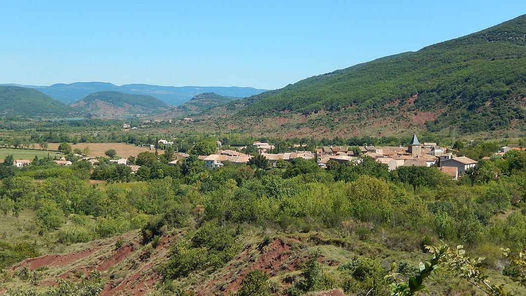 Le village de Salasc (Hérault, France) vu depuis le sentier des béals, qui traverse des hauteurs situées au sud-ouest. Au premier plan, des ruffes, caractéristiques des sols de la région. Au fond, on aperçoit le lac du Salagou. (La géolocalisation de cette image est approximative.)