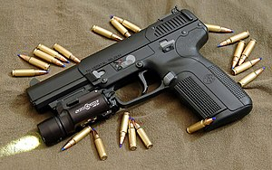Photo of the Five-seveN USG pistol equipped with a tactical light and surrounded by 5.7x28mm SS197SR cartridges