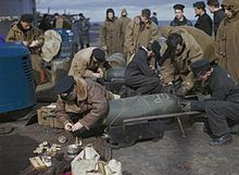 Colour photograph of men wearing military uniform crouching over bombs on the flight deck of an aircraft carrier