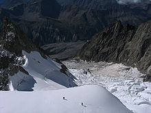 climbers crossing snow above a steep glacier