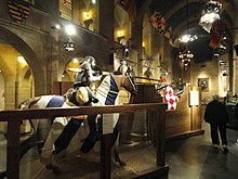 The interior of the Higgins armory. Large stone walls lined with suits of armor and a set of mannequins of men on horses jousting.