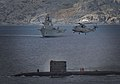 HMS Talent conducts a high line transfer with a Merlin helicopter as HMS Ark Royal passes in the background MOD 45147589.jpg