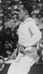 A man in white pants and a white shirt steps back, holding a wooden racket in his right hand