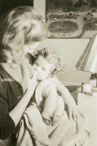 Photograph Australian artist Joy Hester nursing her son Sweeney. In the background can be seen a painting by 'Professor' Henry Tipper (Harold Deering), a trick cyclist and amateur painter whose work was discovered and promoted by Albert Tucker. Shot in 1945, the photo is in the public domain.
