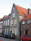 foto van Huis met zadeldak en gecemente topgevel, waarin vensters met schuiframen