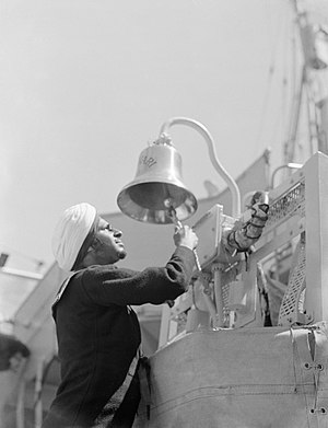 HMIS Godaveri - Leading Seaman Harjit Singh striking the bell of Godavari on commissioning at Woolston, Southampton, 22 June 1943 (IWM A17517)
