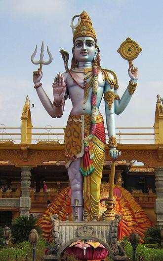 "Harihara - Vishnu ( holding Sudarshana Chakra) and Shiva (lighter coloured half, wearing tiger skin,  holding Trishula) combined in a single Harihara murti, sometimes referred to as Sivakesavaand ""Haryadhamurti""."