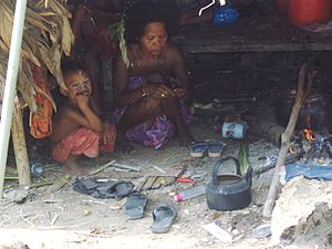 Orang Asli - An Orang Asli woman and a child indoors.