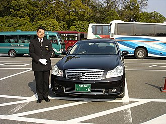 Chauffeur - A chauffeur in Japan standing next to a Nissan Fuga.