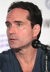 A close-up portrait of Jason Patric behind a microphone.