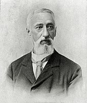 A grey-haired man with a dark jacket and a tie