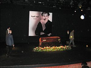 """Juliano Mer-Khamis - Juliano Mer-Khamis lying in state at the al-Midan Theatre, Haifa. The Arabic script on his picture reads shaheed al-ḥuriya, which means """"Martyr for Freedom""""."""