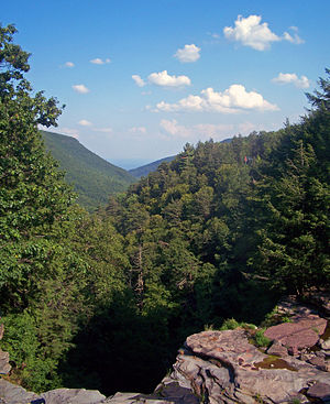 A view over a long, narrow valley with steep wooded sides. A rocky ledge is in the foreground