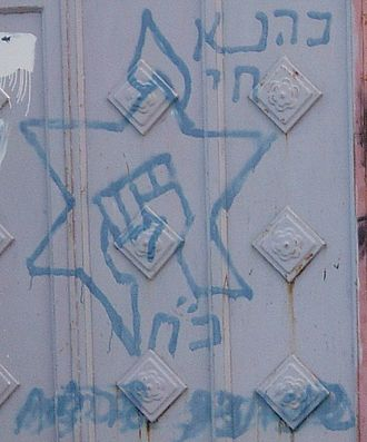 "Kach and Kahane Chai - Kahanist graffiti in Hebron on a Palestinian home. The words to the top right say ""Kahane Chai"". The fist inside the Star of David is the party logo. Below is the acronym for ""Kahane Chai"" which is also the Hebrew word for strength."