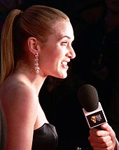 A profile view of Winslet as she speaks into a microphone.