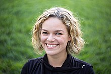 Katherine Maher in 2016. She is seen with light skin, blonde hair, and blue eyes. She is seen wearing a black shirt.