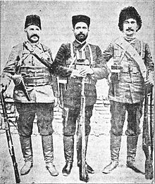 Three stanidn men with rifles