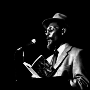 English: Linton Kwesi Johnson on stage reading...