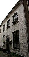 Huisje met eenvoudige lijstgevel. Rondboogpoortje met 1606.