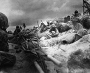 Marines take cover behind seawall at Red Beach no. 3, Tarawa