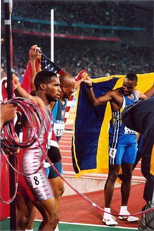 Athletics at the 2000 Summer Olympics – Men's 100 metres - The three medallists celebrating