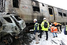 "Several people in neon colored safety clothing and white helmets examine the fire-damaged wreckage of a silvery passenger rail car along the top with ""Metro-North Railroad"" written on it. One person has the letters ""NTSB"" on their jacket sleeve. At left is the rear of a similarly fire damaged automobile."