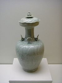 A white, handle-less jar with a small base, a wider body, and then a long, thin, opening at the top. Four flower-shaped ornaments are attached to the point where the body and the stem of the jug meet.