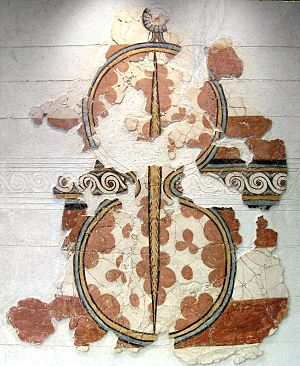 "Shield - Wall painting depicting a Mycenaean Greek ""figure eight"" shield with a suspension strap at the middle, 15th century BC, National Archaeological Museum, Athens -The faces of figure eight shields were quite convex. The cited ""strap"" may be the ridge on the front (so denoted by the visible pattern of the ox hide) of the shield."