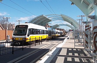 """DART Light Rail - a two-car SLRV on the existing long platform at """"NL College"""" on orangen line (the roof parts are each over the low floor sections of the train)"""
