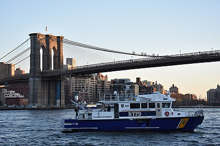 Police boat patrolling the East River NYPD police boat, Brooklyn Bridge and Downtown Brooklyn at sunset.JPG