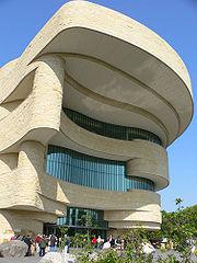 Vue extérieure d'un musée amérindien, constitué de deux niveaux en plus du sol, un toit surplombant largement l'entrée.