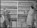 New Mexico. Mrs. Fidel Romero proudly exhibits her canned food.. (Two women standing in a kitchen pantry. Pantry... - NARA - 513405.tif