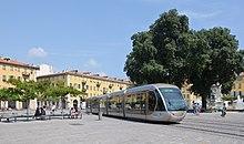 Vue d'un tramway traversant une place avec des arbres derrière.